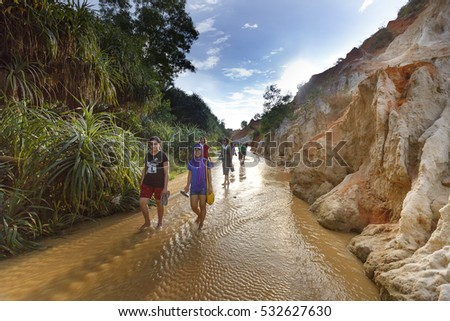Mui Ne, Phan Thiet city, Vietnam - November 27, 2016 : tourists so excited to be walking on feet in the Red Stream ( it also named Fairy Stream) located near the beach of Mui Ne, Binh Thuan Province