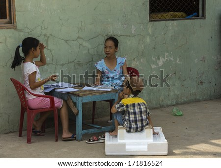 MUI NE, VIETNAM - CIRCA MARCH 2012:  Two primary schoolgirls doing their homework in front of their home while a little boy watches attentively.