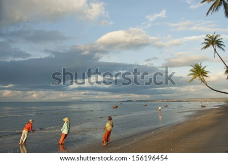 MUI NE, VIETNAM - NOVEMBER 4: Unidentified Vietnamese people pull their seine out on the beach in Mui Ne, Vietnam on November 4, 2008. For most of Vietnamese seafood is main source of livelihood. - stock photo