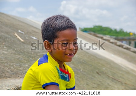 Muisne, Ecuador - March 16, 2016: Kid sitting outdoors with yellow football shirt on and smiling