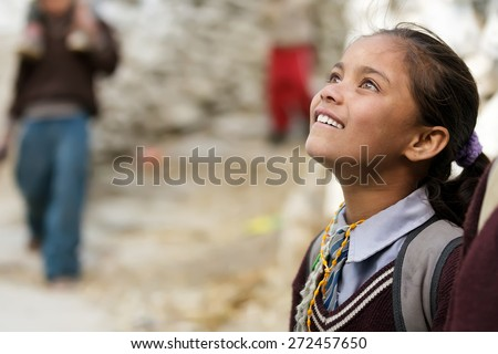 MUKTINAH, NEPAL, NOVEMBER 10 : A little girl coming back from school is looking at her friends with an admiring expression in Muktinah village, Annapurna , Nepal on 10 November 2010 - stock photo