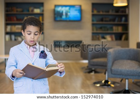 Mulatto boy in a striped jacket read a book in library