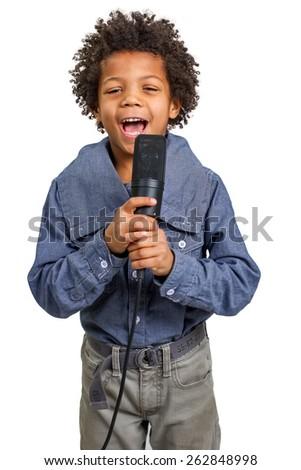 Mulatto boy singing into a microphone. - stock photo