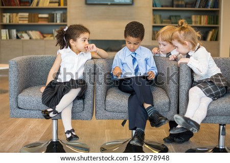Mulatto boy sits on a chair and using a tablet, but the other kids look up to him