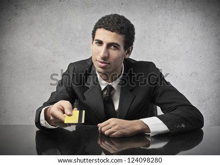 Mulatto businessman handing someone a credit card
