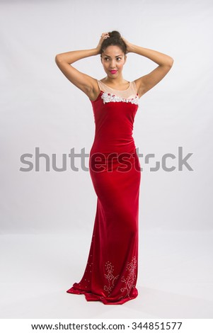 Mulatto girl dancer performs a dance elements, isolated on a light background