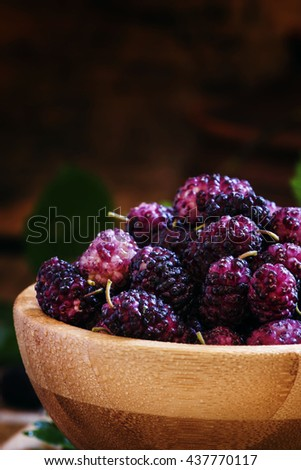 Mulberry in bowl, with leaves, vintage wooden background, selective focus