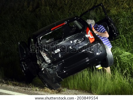 MULES, ITALY - JUNE 16, 2014: A person giving first aid to a injured motorist after a serious car crash accident in the night on June 16, 2014 - stock photo