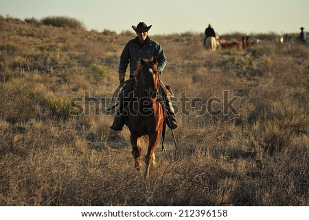 Muleshoe, Texas, USA, - March. 23. 2012: Cowboys on the horse in sunset - stock photo