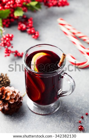 Mulled red wine with orange slices and spices on a Christmas background