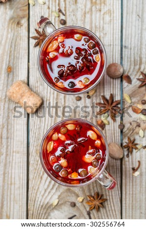 mulled red wine with spices on a wooden table - stock photo