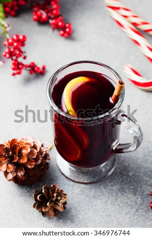 Mulled red wine with spices, orange slices  on grey stone new year and christmas background