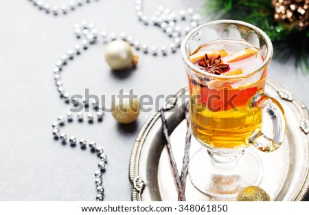 Mulled white wine with grapefruit and spices in a glass on a Christmas, New Year background - stock photo