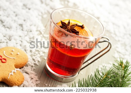 mulled wine and gingerbread man on wooden table with snow - stock photo