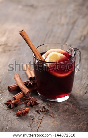 Mulled wine and spices on wooden background. Selective focus. - stock photo