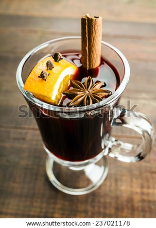 Mulled wine and spices on wooden background. Selective focus - stock photo