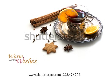 Mulled wine, Christmas punch with orange slices and spices like cinnamon, star anise and cloves on a vintage silver plate, isolated with shadows on a white background, sample text Warm Winter Wishes - stock photo