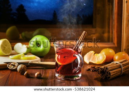 Mulled wine for Christmas Eve celebration party on a table. Traditional winter Christmas drink near the window, winter landscape with sky full of stars on background.
