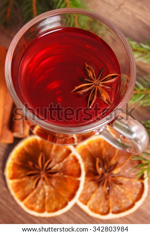 Mulled wine for christmas or winter evening on wooden surface plank, spruce branches and spices, cinnamon anise dried orange - stock photo