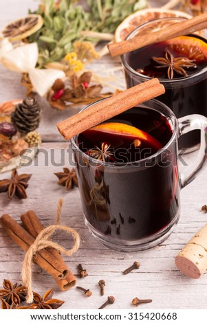 mulled wine glasses with spices, orange and christmas decoration