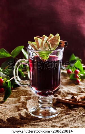 mulled wine in clear glass with apple and cinnamon in a still life on the sand - stock photo