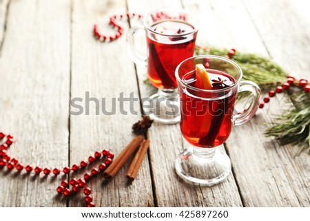 Mulled wine in glass on grey wooden table - stock photo