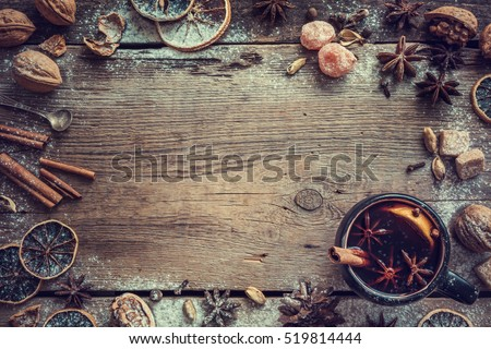 Mulled wine in rustic mug with spices and ingredients on wooden background. Top view, flat lay. Retro toned photo. Copy space for your text.