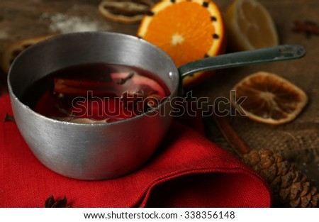 Mulled wine in stew-pan on decorated with red napkin, cinnamon and orange wooden background