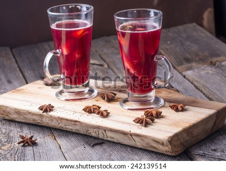 Mulled wine on wooden board and ancient table - stock photo