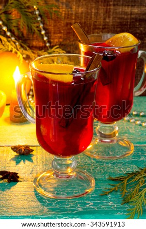 Mulled wine with a candle and a decorated Christmas tree in a rustic style