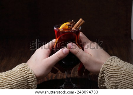 Mulled wine with addition of an orange, honey, cinnamon, a carnation and an anise, man's hands hold  with mulled wine - stock photo