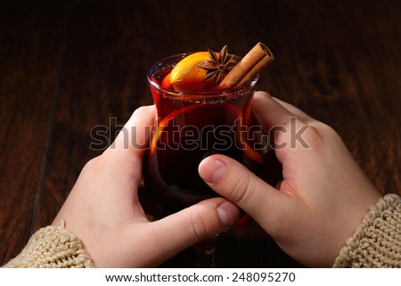 Mulled wine with addition of an orange, honey, cinnamon, a carnation and an anise, man's hands hold ��±��±��¾��º��°��» with mulled wine - stock photo