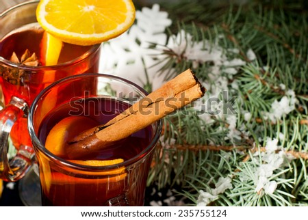 Mulled wine with cinnamon and star anise with slice of orange and spices and Christmas cakes, with decorated background - stock photo
