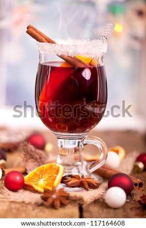 mulled wine with cinnamon and star anise with slice of orange and spices, with decorated background - stock photo