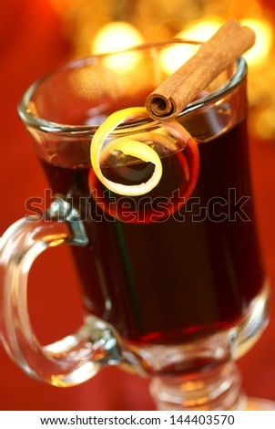 Mulled wine with lemon peel and cinnamone stick on glass. Selective focus, shallow DOF. - stock photo