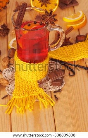 Mulled wine with orange, cloves, anise and cinnamon, nuts, chocolate chips, a yellow scarf on a background of light wood.