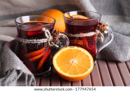 Mulled wine with oranges on table on fabric background - stock photo