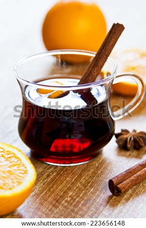 Mulled wine with pieces of orange and spices - stock photo