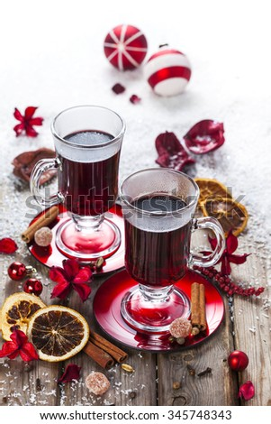 Mulled wine with spices and Christmas decorations on snowy table