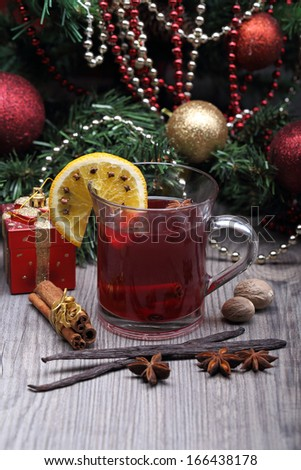 mulled wine with spices and christmas tree with decoration