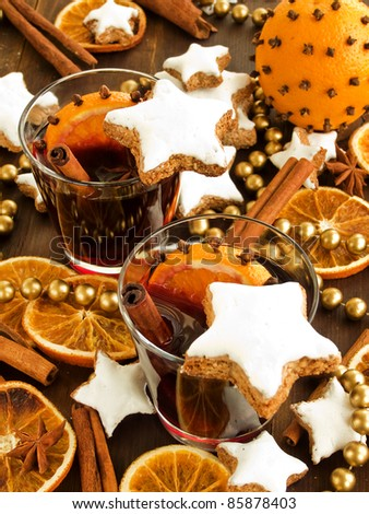 Mulled wine with spices and cinnamon cookies. Shallow dof. - stock photo