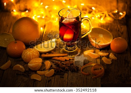 Mulled wine with spices and orange on wooden background, selective focus