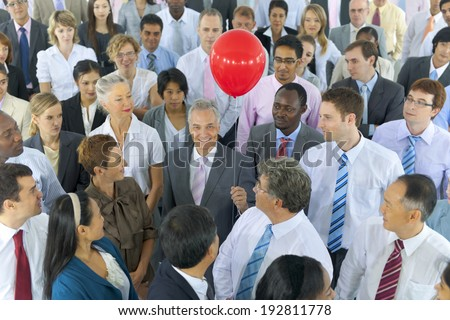 Mullti-ethnic group of business person standing around the one holding red - stock photo