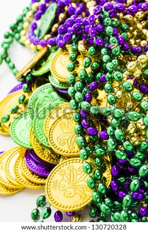 Multi color Mardi Gras beads and tokens on white background. - stock photo