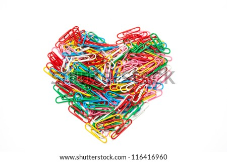 Multi color paper clips arranged in heart shape on isolated white background - stock photo