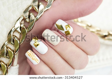 Multi-color pastel manicures with gold metallic rhinestone and chain in his hand.