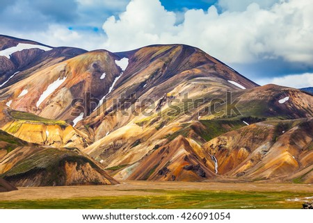 Multi-color picturesque rhyolitic mountains are lit with the sun. Travel to Iceland in the summer - stock photo