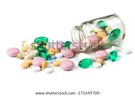 Multi color pills spills out of the little jar, bottle, isolated on white