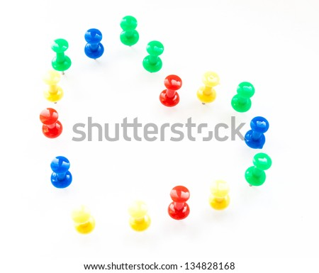 Multi color thumb-tacks arranged in heart shape on white. - stock photo