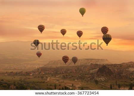 Multi-colored balloons fly over rocks in Cappadocia at sunrise